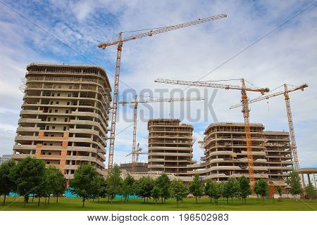 Construction of new residential area. Construction industrial cranes, gray monolithic houses made of concrete. Concept of construction. New housing and square meters.