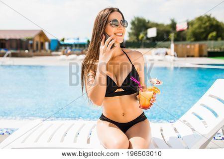 Young Woman In Swimsuit Relaxing With Cocktail Near Pool And Use Phone