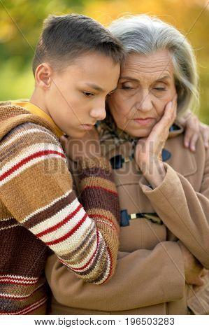 sad grandmother  and grandson hugging  in park