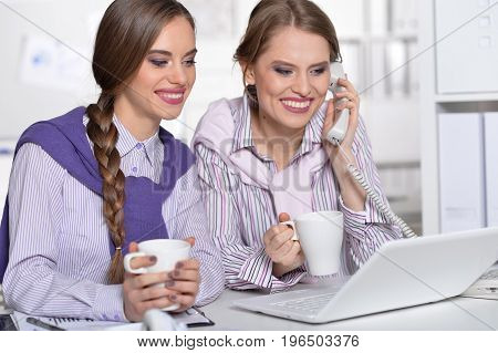 Two young beautiful business women working in office