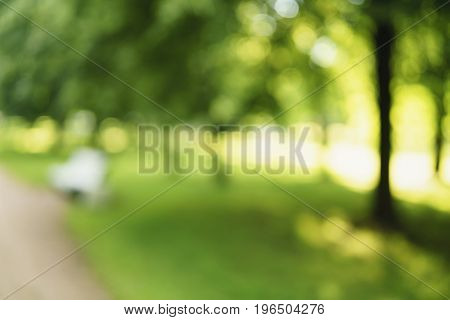 abstract blurred background of city park in sunny summer day, real lens blur