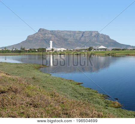 FROM CAPE TOWN, SOUTH AFRICA, REFLECTIONS OF TABLE MOUNTAIN  ACROSS THE MILNERTON LAGOON