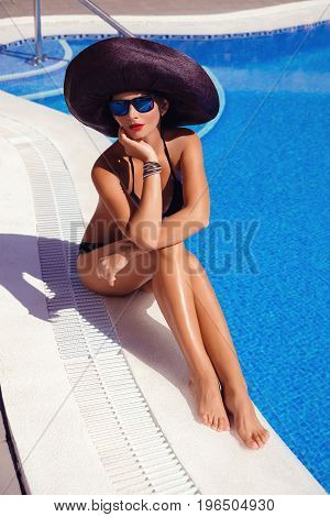 Beautiful tanned young woman with perfect body wearing white bikini and hat relaxing near swimming pool. outdoor shot. copy space.
