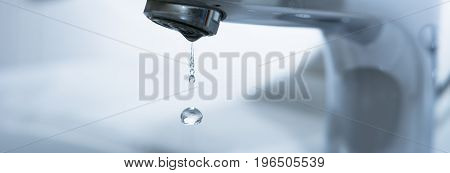 Faucet wit falling water drops in bathroom with and white blue background