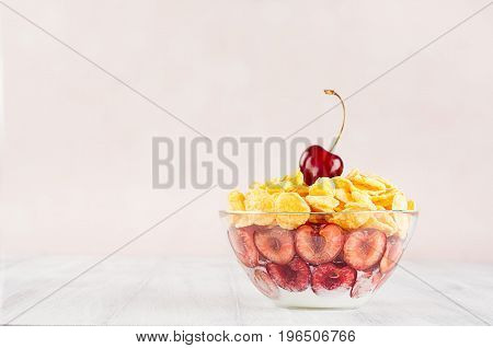 Delicate pink breakfast with golden corn flakes decorated cherry on white wood board. Decorative border with copy space.