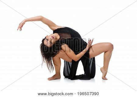 Beautiful modern dancer young woman in black flyings fabrics making dance moves. Isolated on white background. Copy space.