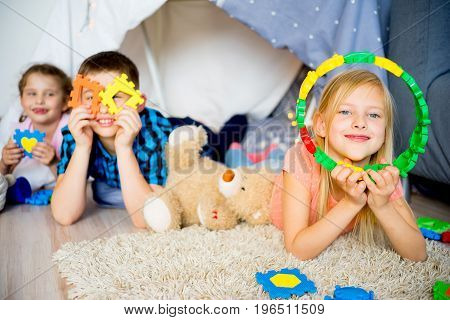 Three friends in a play tent at a sleepover