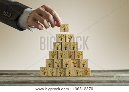 Man Stacking A Tower With Yellow Light Bulbs In A Form Of A Pyramid
