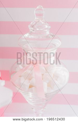 Transparent vase with marshmallows decorated with pink ribbon