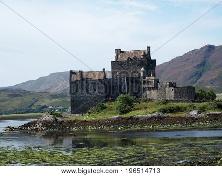 Eilean Donan castle in Scotland, celtic medieval scottish stone building on island at lake loch Duich in Highlands in Great Britain with cloudy sky in 2016 warm summer day, UK Europe on August.