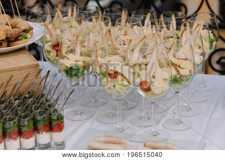 Tasty salad served in the clear wineglasses on the wedding
