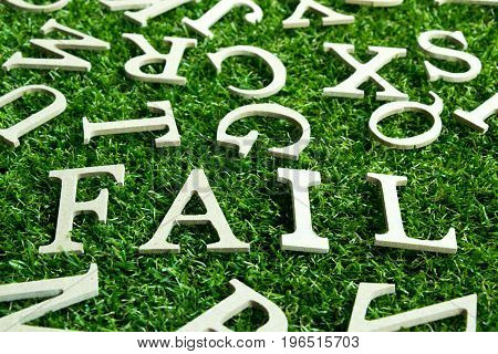 Wording fail on artificial green grass with another english alphabet background