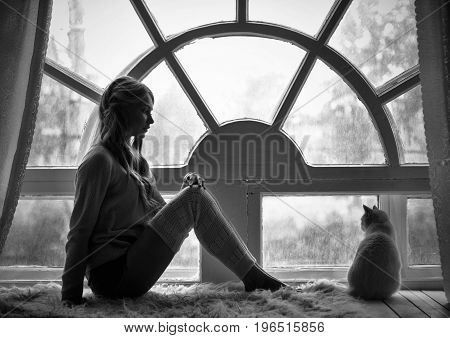 Art photo blond girl and white cat sitting at big old window during the rain. Romantic Black and white photo loneliness and sadness in rain