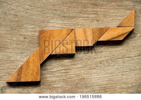 Wood tangram puzzle in gun shape background