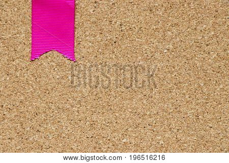 Pink ribbon placed on cork board background with the space for add text