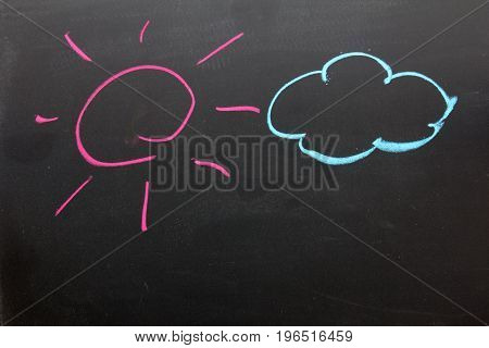 Hand drawing as pink sun with beam and blue cloud on black board background