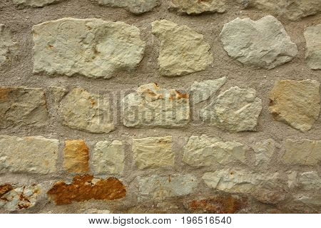 Old porous stone wall as a very interesting background and texture. Horizontal view.