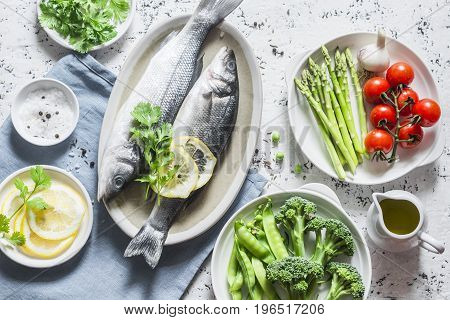 Set of healthy balanced ingredients for lunch - sea bass asparagus tomatoes broccoli green peas olive oil and spices. On a light background top view. Flat lay
