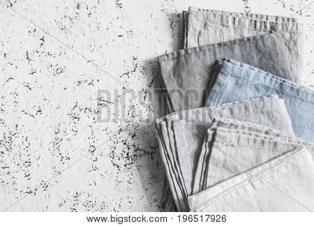 Linen napkins in pastel shades on a light background top view. Free space rustic style