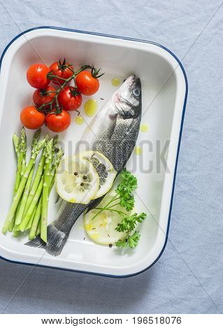 Raw sea bass cherry tomatoes and asparagus in the baking tray. Ingredients for lunch. On a blue background top view