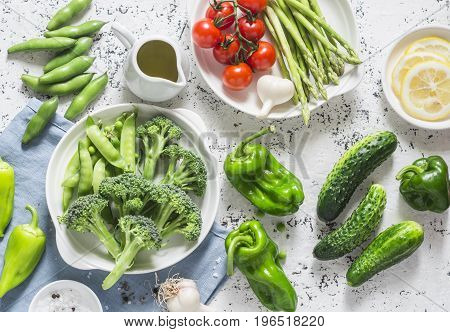 Assortment of fresh garden vegetables - asparagus broccoli beans peppers tomatoes cucumbers garlic green peas on a light background top view. Vegetarian food concept. Flat lay