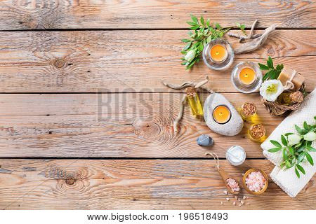 Spa still life wellness setting concept. Assortment of essential oil cream sea salt natural soap candles and towel on a rustic wooden table. Top view flat lay copy space background