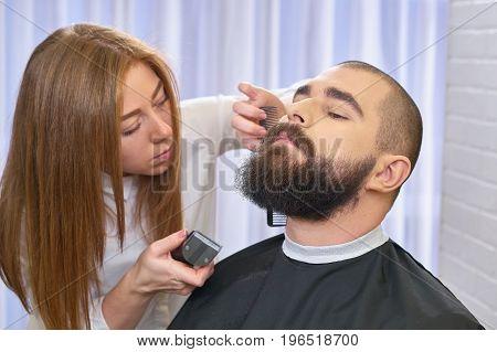 Beard grooming process. Female barber at work. Basics of barbering.