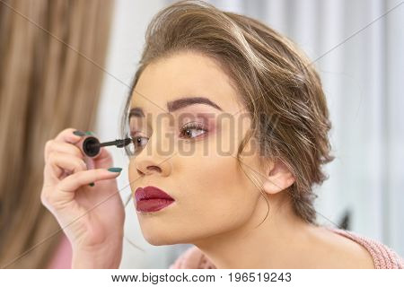 Woman using eyelash brush. Girl applying makeup. Date makeup ideas.