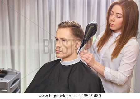 Young man in hair salon. Hairdresser is using blow dryer.
