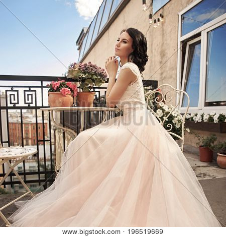 Young pretty stylish bride in fluffy white dress sitting at summer terrace. Beautiful young woman with hairstyle and make posing on a sunny day with blue sky