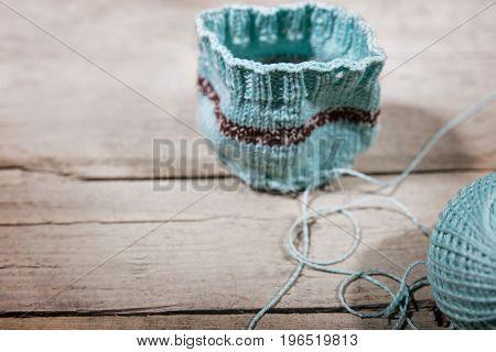Handiwork Crochet, Blue Cup Warmer And Woolen Ball On Wood