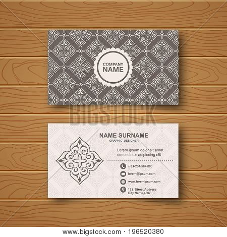 Template of the blank business card on a wooden table.Card with a flower pattern with a realistic shadow. Vector illustration.