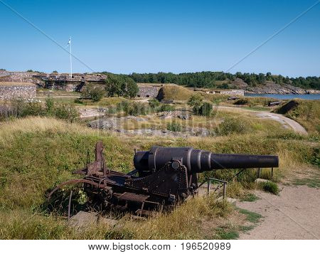Rusty iron cannons installed on an fortress island next to Helsinki