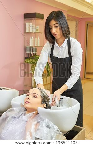 Beautician washing head of woman. Lady working in hair salon. Hair products reviews.