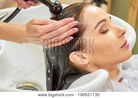 Woman getting her head washed. Girl with wet hair, macro.