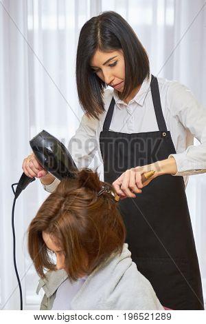 Hairdresser using a blow dryer. Hair salon employee and customer.