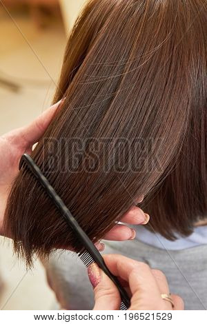 Hand with comb brushing hair. Female hair, close up. How to make hair thick.