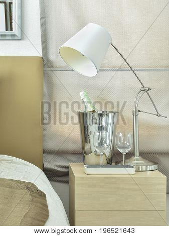 White Table Lamp With Empty Glasses And Wine Bottle On Bedside Table