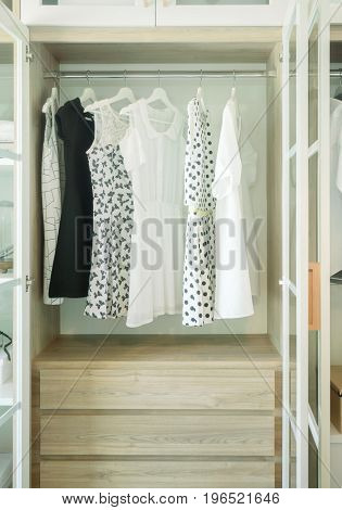 White Wooden Closet With Row Of Dress And Blouses