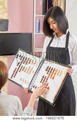 Woman holding hair swatches chart. Girl choosing hair dye color. Hair expert advice.