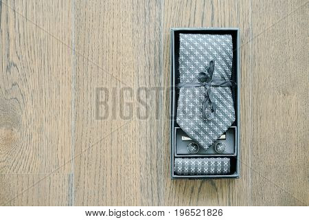 Tie And Cufflinks In Box On Wooden Background
