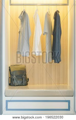 Men's T-shirts Hanging In Wooden Wardrobe With Leather Bag
