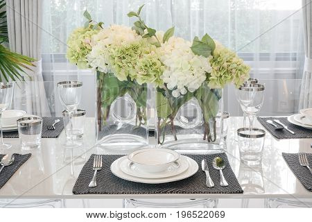Chinaware And Glassware Setting On Dining Table With White And Green Flowers At Center Of Table