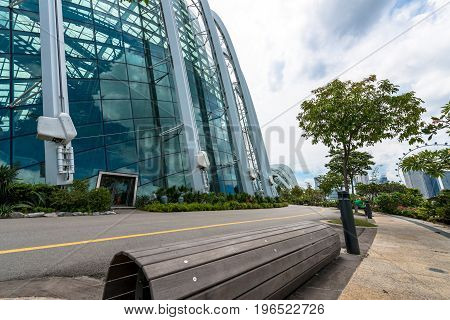 SINGAPORE - MARCH 22 2017: Wooden bench on the sidewalk of Flower Dome tourist attraction at Gardens by the Bay in Singapore.