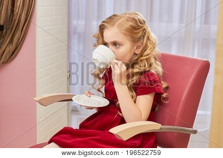 Little girl is drinking coffee. Child holding white cup indoor. Is caffeine bad for kids.