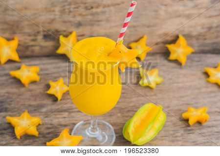 Mango Smoothies And Pieces Of Carambola On An Old Wooden Background