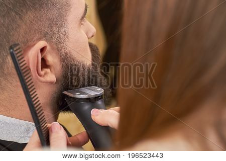 Beard grooming process, close up. Barber using a trimmer.