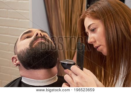 Bearded man in barbershop. Female barber working with client.