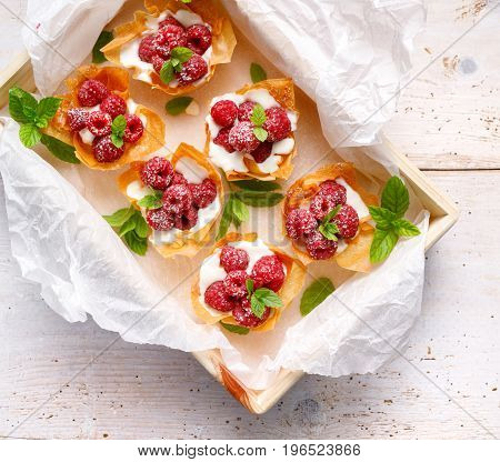 Phyllo cups with Mascarpone cheese  filling topped with fresh raspberries and mint, top view