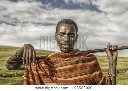 Serengeti, Tanzania , December 2015 : Young african man posing in a Masai tribe village. The Masai are a Nilotic ethnic group living in southern Kenya and northern Tanzania